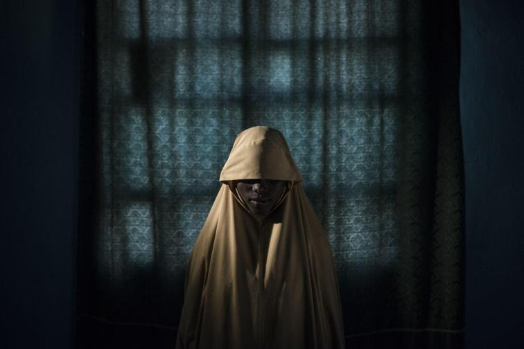 (C) Adam Ferguson: Aisha (14) stands for a portrait in Maiduguri, Borno State, Nigeria. After being kidnapped by Boko Haram, Aisha was assigned a suicide bombing mission, but managed to escape and find help instead of detonating the bombs.