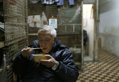 "A 77 year old man eats dinner outside his ""cage"" accommodation (C) Vincent Yu"