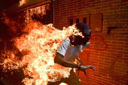 (C) Ronaldo Schemidt: José Víctor Salazar Balza (28) catches fire amid violent clashes with riot police during a protest against President Nicolas Maduro, in Caracas, Venezuela.